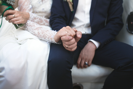 holding close: bride and groom holding hands close view