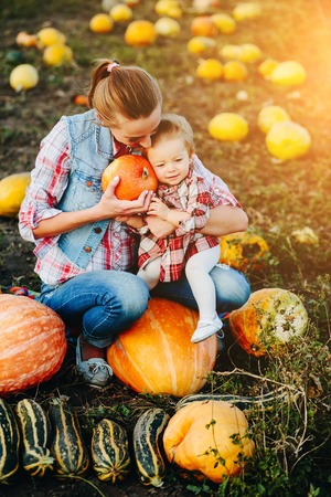 Mother and daughter sitting on pumpkins, Halloween eve Stock Photo