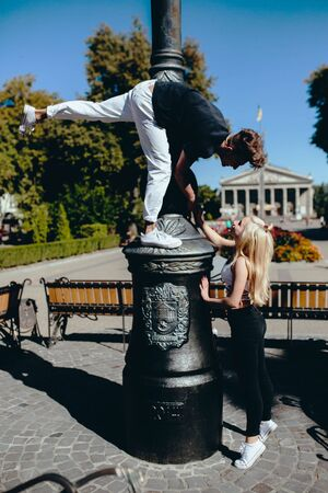position d amour: man and woman performing acrobatic tricks on the street