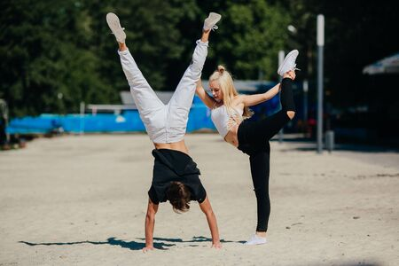 man and woman performing tricks in the park Stock Photo