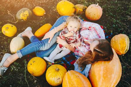 vegetare: mother and daughter lie between pumpkins on the field, Halloween eve