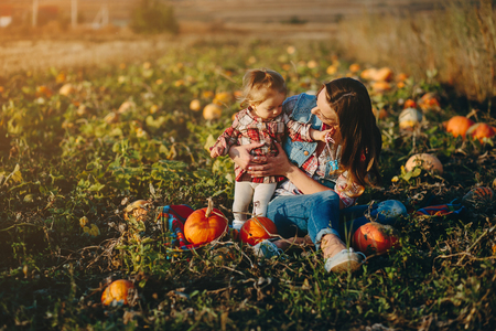 vegetare: mother and daughter on a field with pumpkins, Halloween eve Stock Photo