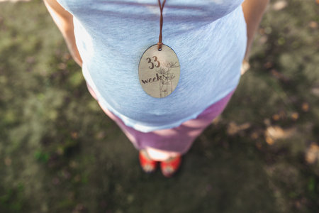 Pregnant womans belly with a close angle in the park Stock Photo