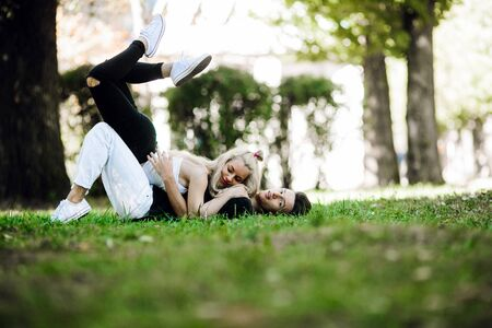 position d amour: man and woman lie on the grass in the park Banque d'images