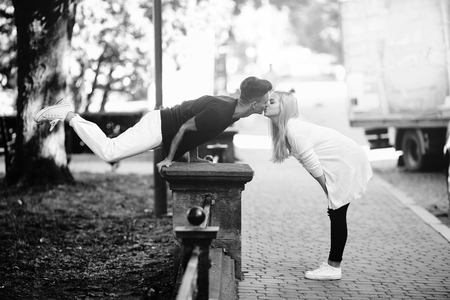 position d amour: man performs an acrobatic trick in a park near a girl