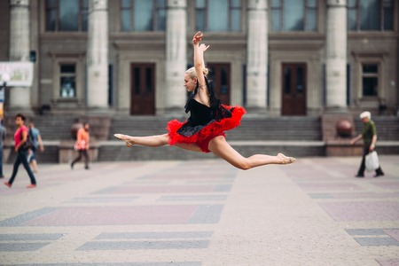 Ballerina doing splits in the air on the square