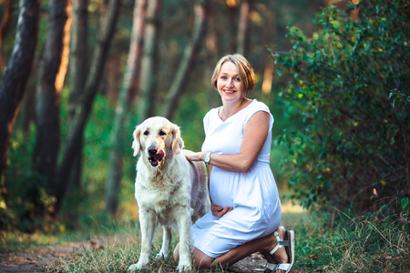 Beautiful pregnant woman and her dog pet togheter outdoor