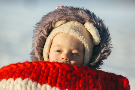 portrait of cute little girl child sitting on sledges at winter day with fresh snow Stock Photo