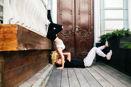 position d amour: girl standing on the hands, a guy lying on the ground on a background of doors