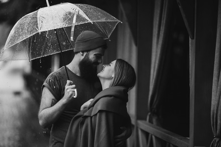 guy and the girl posing together in the rain on a city street