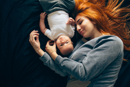 Happy mother with baby lying together on bed at home Stock Photo