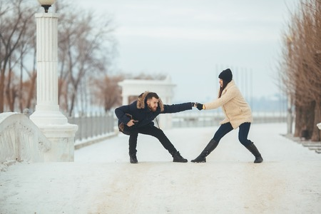 man and woman fooling around a snow-covered park in the park