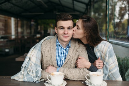 sidewalk talk: Romantic young couple sitting at sidewalk cafe, drinking cappuccino outdoors