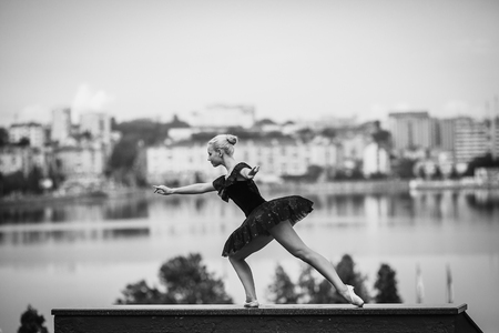 gracefully: ballerina posing on a background of the lake at the camera