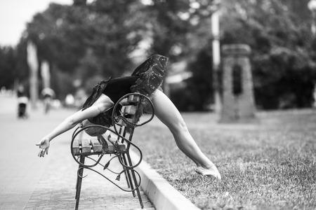 Ballerina bends back through bench in the park