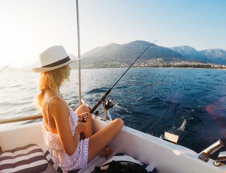 Aantrekkelijk meisje op een jacht in de zomer dag Stockfoto
