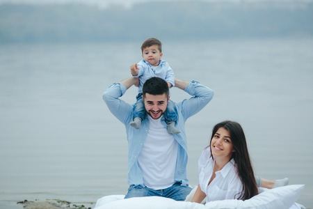 Happy young family relaxing together on the lake Stock Photo
