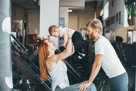 hombres haciendo ejercicio: Joven de la familia con el niño pequeño en el gimnasio Foto de archivo