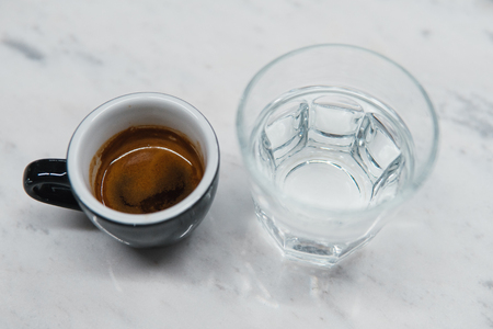 cup with coffee near a glass of water on the table