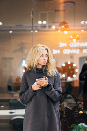 Blonde girl standing with smartphone Stock fotó