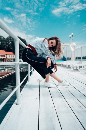 Young beautiful girl posing on the pier