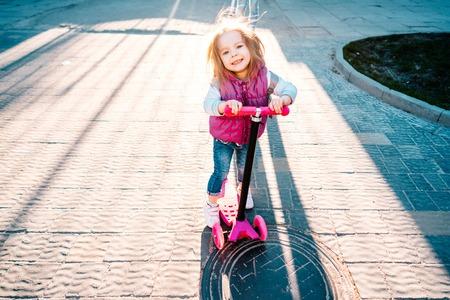 ブロンドの髪を持つ少女はスクーターに乗ってください。 写真素材
