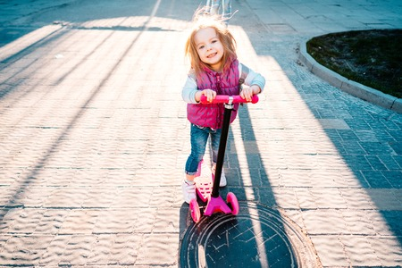 Little girl with blonde hair rides on scooter
