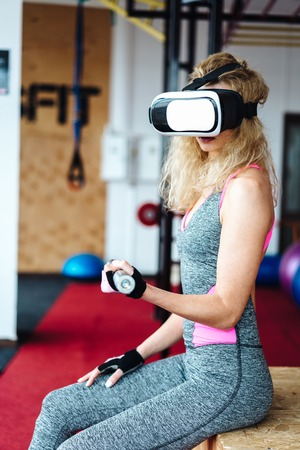 Beautiful girl in the gym with VR headset Фото со стока