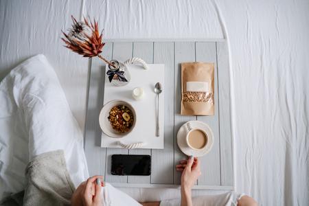 침대, 밝은 배경에서 시리얼을 먹는 여자