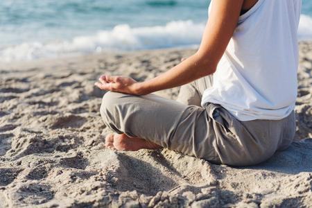 lichaam van een mooi meisje in een meditatie op het strand