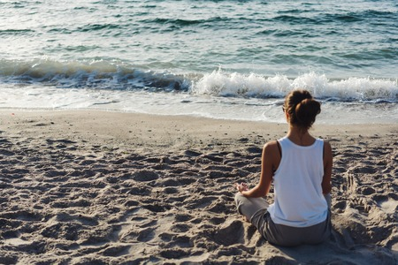 rejuvenated: Young woman practicing yoga on the beach.