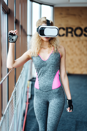 Beautiful girls in the gym at the window with VR headset