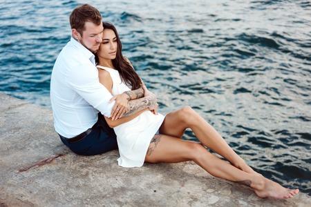 Giovane coppia sono seduti sul molo in riva al mare