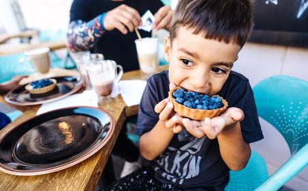 kleine jongen die dessert met bosbessen eet