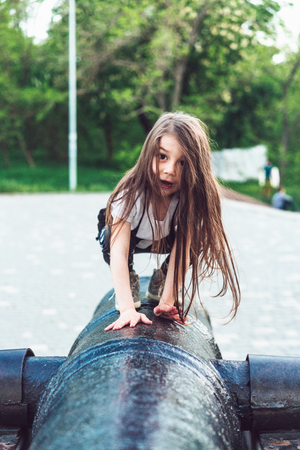 preschool girl crawls on top of cannon