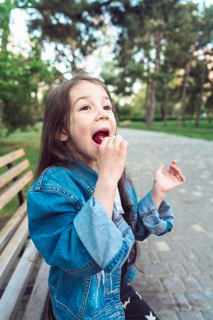 Girl sitting on bench eating candies