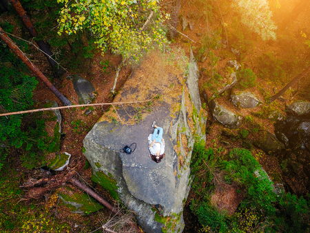 Top down aerial drone image of a forest, woman lies on a rock Imagens