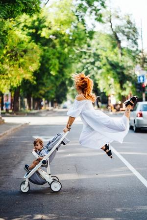 moeder met een kinderwagen steekt de weg over