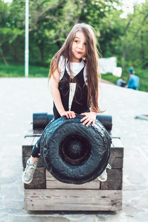 preschool girl sitting on top of a cannon