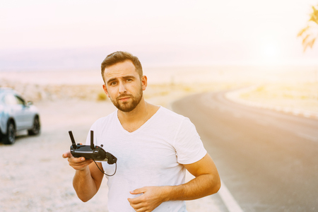 Guy controls drone with remote control Stock Photo