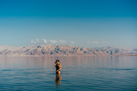 Young woman going to Dead Sea, Israel Imagens - 94722178