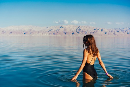 Young woman going to Dead Sea, Israel Imagens - 94722181
