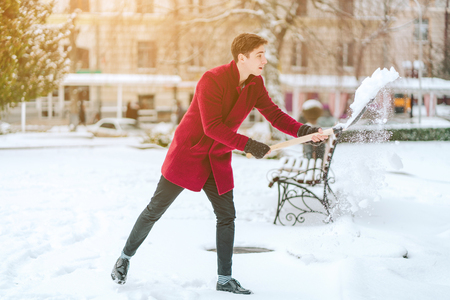 young man shoveling snow