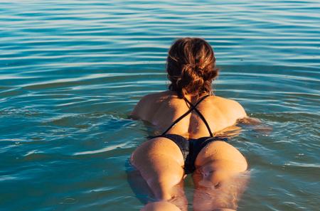 女の子はリラックスして水の中で泳いでいます