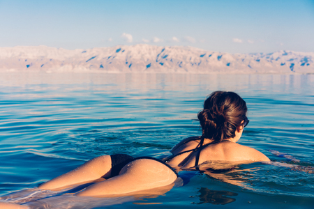 Girl is relaxing and swimming in the water Imagens
