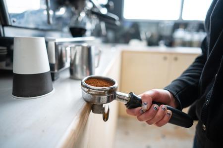 Barista holding portafilter with ground coffee Stockfoto - 104116567