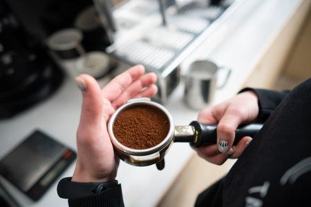 Barista holding portafilter with ground coffee Stockfoto - 104116570