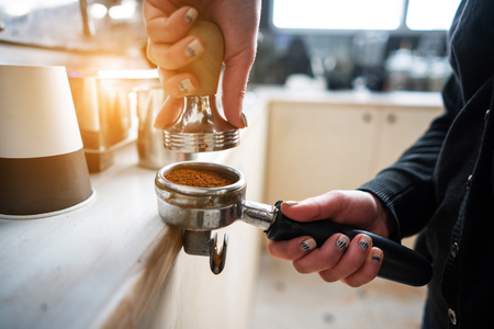 Barista presses ground coffee using tamper.