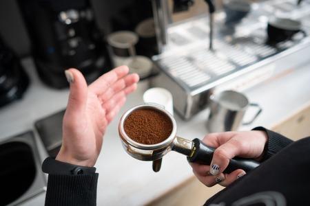 Barista holding portafilter with ground coffee Stockfoto - 106088387