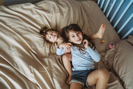 happy little girls lying on back top view sisters Foto de archivo